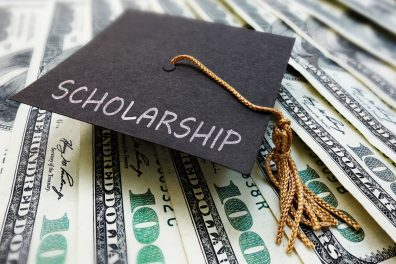 Mortar Board hat says scholarships and it is sitting on money.