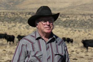 Portrait of rancher, with cattle on the range in the background