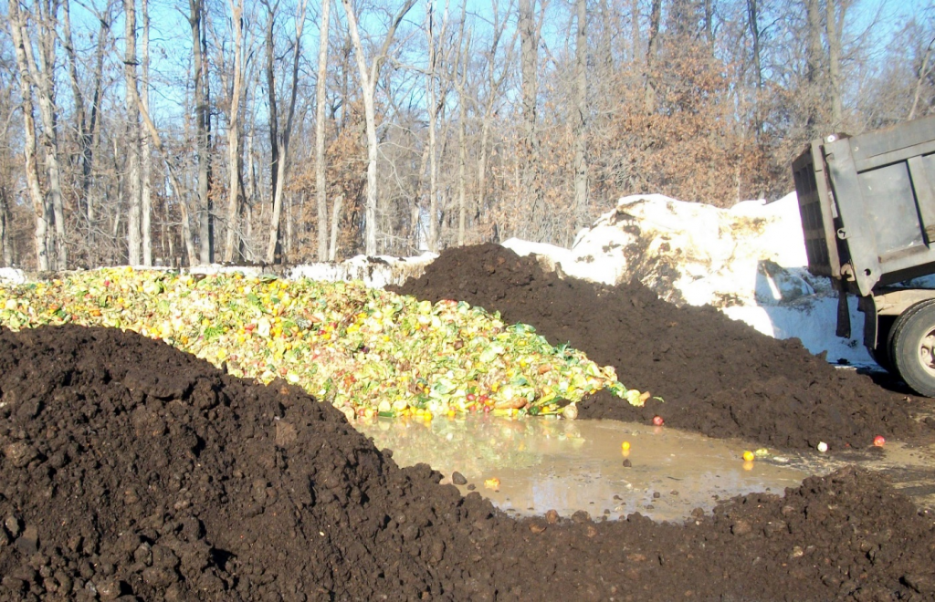 Dump truck finishes unloading organic waste onto compost pile.