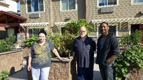 Three people stand on front of raised gardening beds in an apartment complex.
