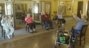 Senior site in chairs exercising in a senior center.