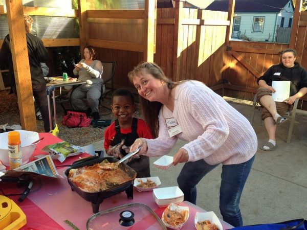 Talea Price poses with a young boy while serving food from the cooking demo table.