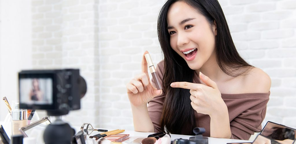 Beautiful Asian woman beauty vlogger recording makeup tutorial