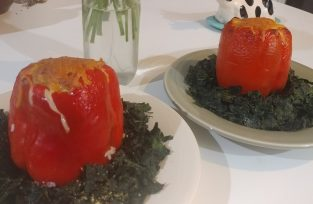 Stuffed red pepper on a bed of baked kale