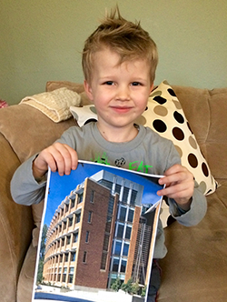 Young boy holding a photo of the Paul G. Allen Center for Computer Science & Engineering