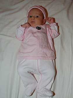 Full-length shot of baby in pink outfit and hat with CSE t-shirt