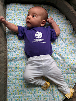 Baby in purple CSE t-shirt and yellow bow-tie shoes