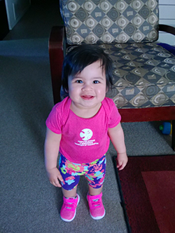 Smiling toddler in pink CSE t-shirt and matching sneakers