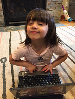Little girl in CSE t-shirt playing with a laptop computer