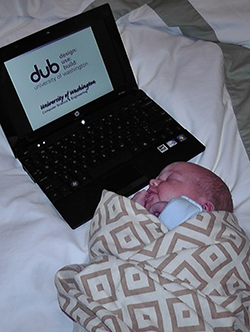 Newborn wrapped in blanket next to laptop displaying DUB group logo