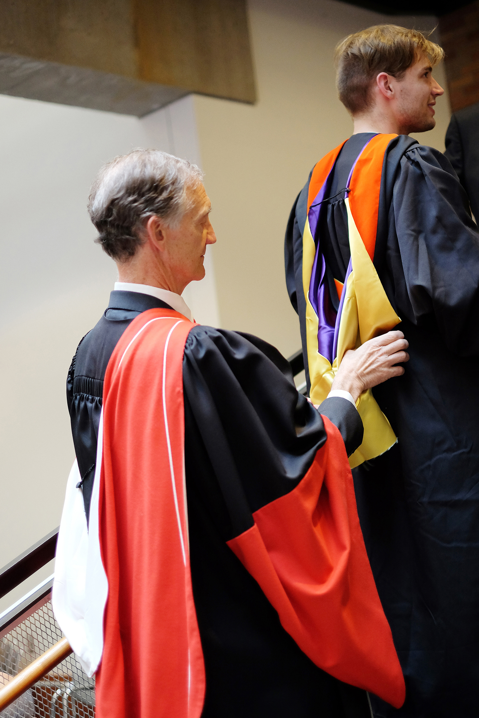 A faculty member assists a new graduate with his hood