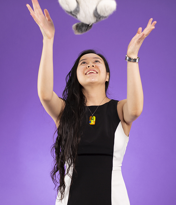 Savanna Yee tossing plush dog above her head