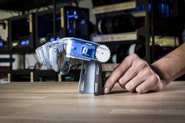 Close-up of a 3D-printed prototype of a prosthetic hand next to a human hand