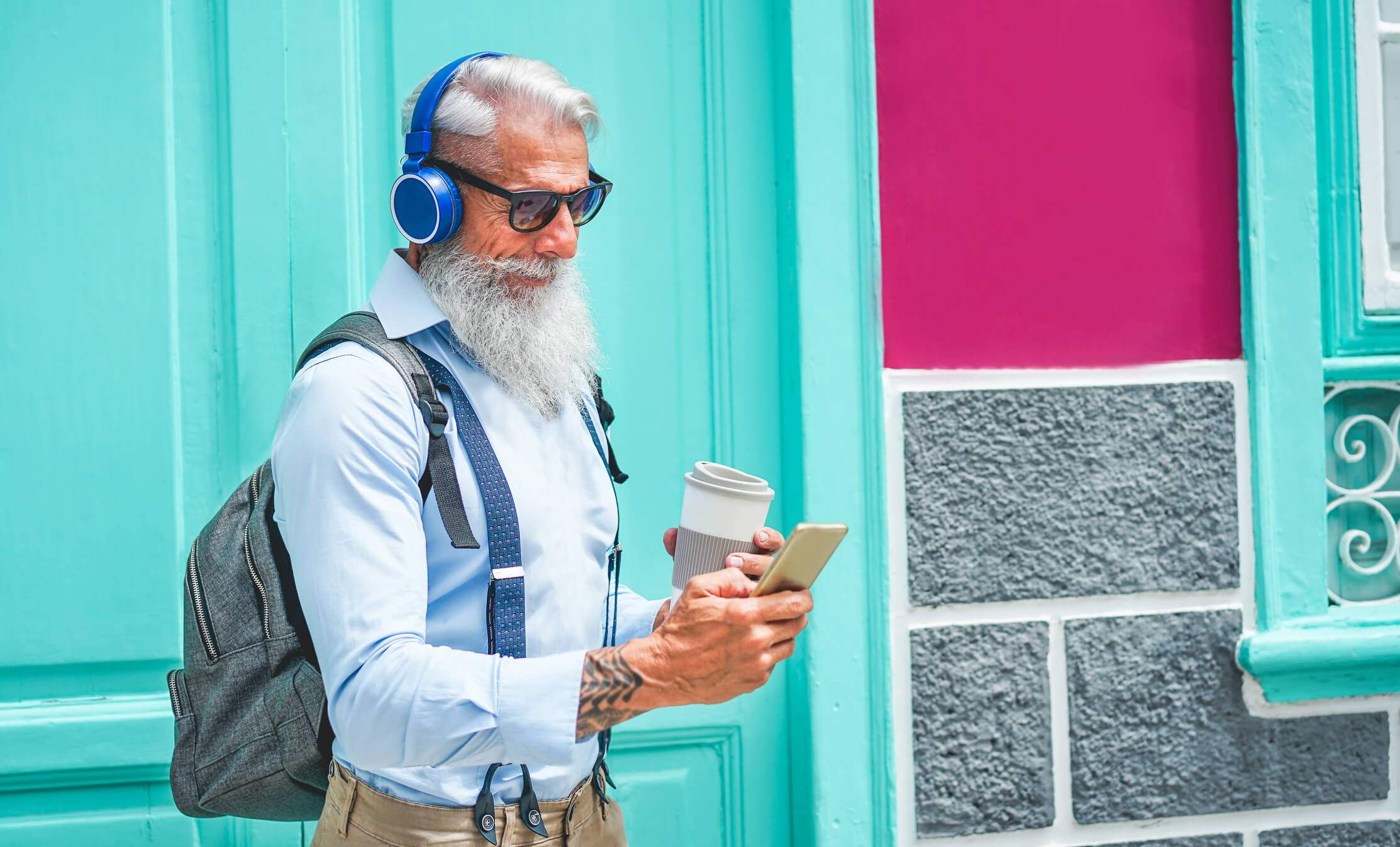 An image of an older man using his phone and wireless headphones.