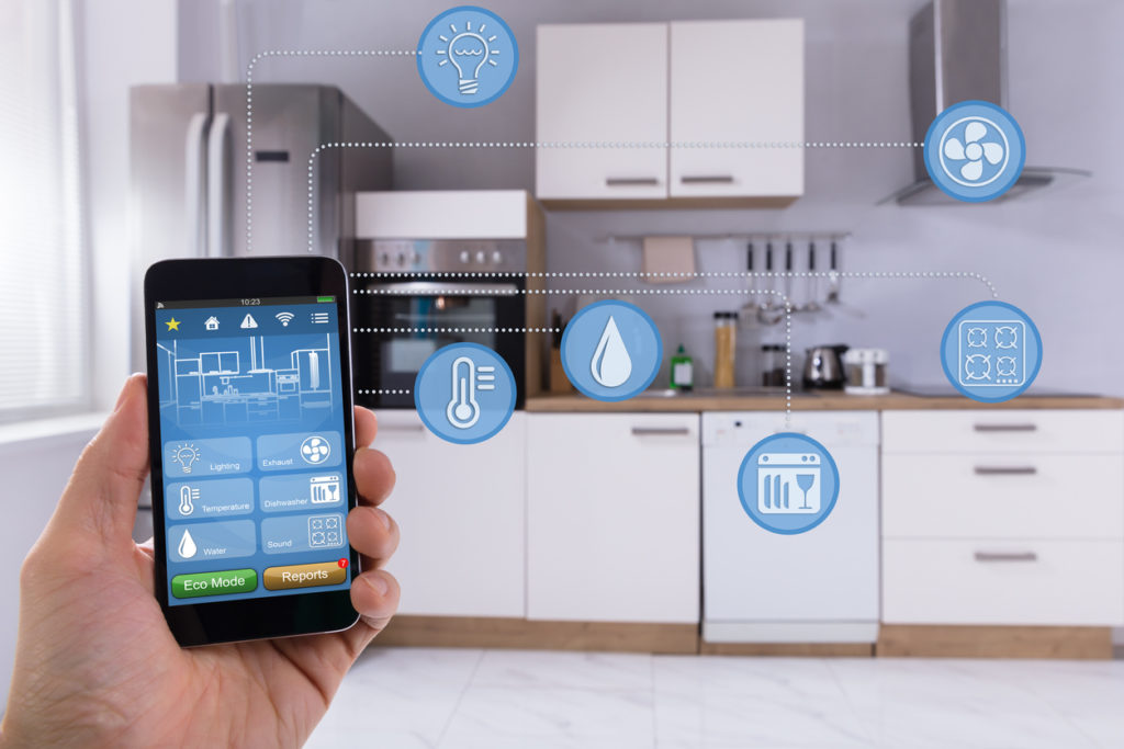 a smart phone is being used in a kitchen to control IoT appliances