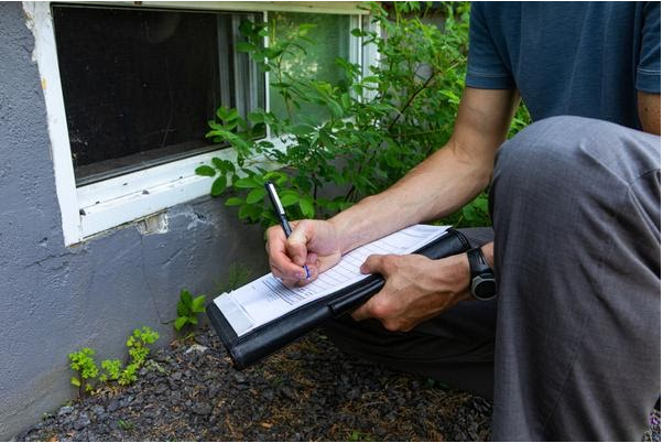 Home inspector examining a home's foundation while filling out a home inspection report outside a house.