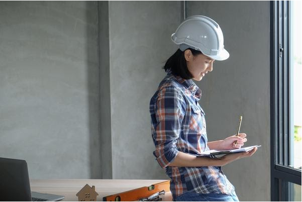 Female home inspector filling out a home inspection report.