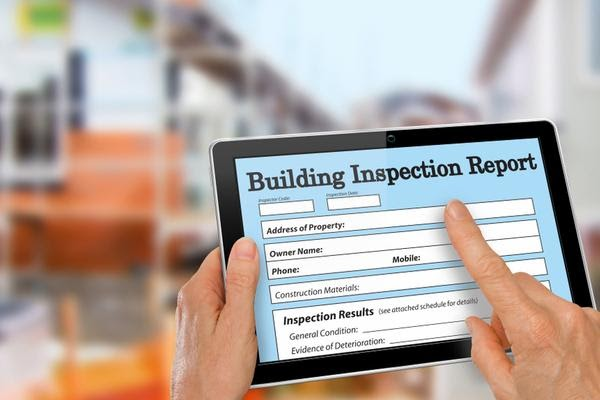 Person filling out a building inspection report on a tablet using digital building inspection software.