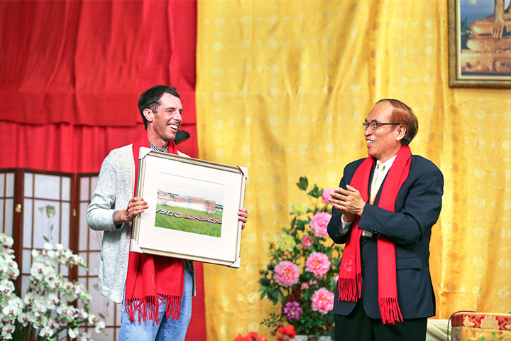 PEI 大學校方人員,接受福智致贈之大覺佛學院圍巾、加拿大國慶排字照片。